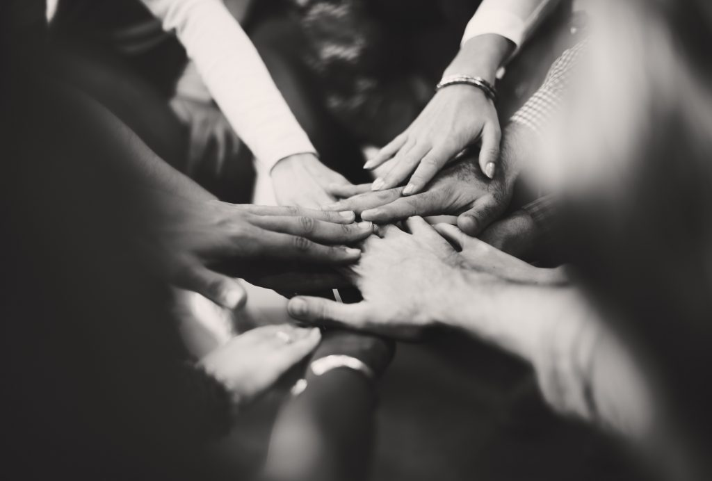 Hands all together in center to symbolize collaboration through affiliate marketing.