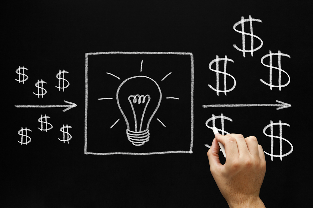 Image of hand drawing light bulbs and dollar signs on chalk board. Symbolizes passive income.
