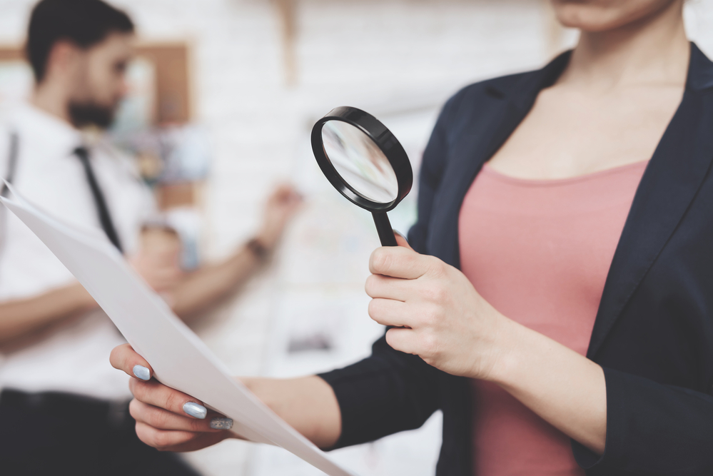 Woman looking at emails on a page with a magnifying glass