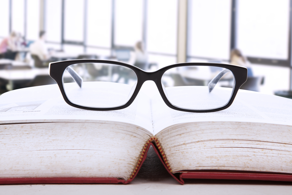 glasses on top of a book - voice of customer research sprint.