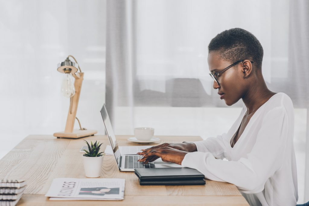 Email copywriter for hire sitting at desk typing on laptop with newspaper, plant, notepad, lamp, and coffee cup sitting next to her,