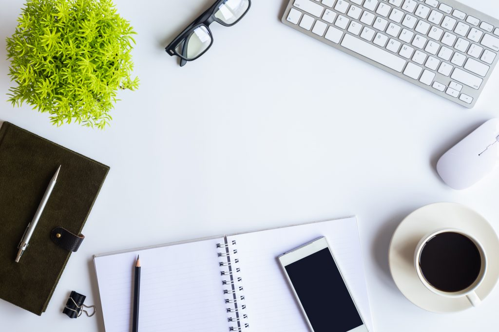 Email copywriter and freelance writer for hire.  Image of desk with notepad, pencil, phone, coffee, keyboard, mouse, glasses, leather planner, pen, and plant.