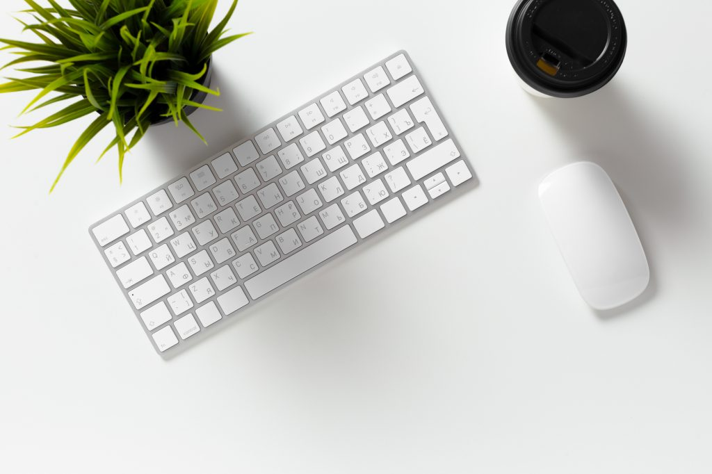 Email copywriter's desk with keyboard, mouse, coffee, and plant.