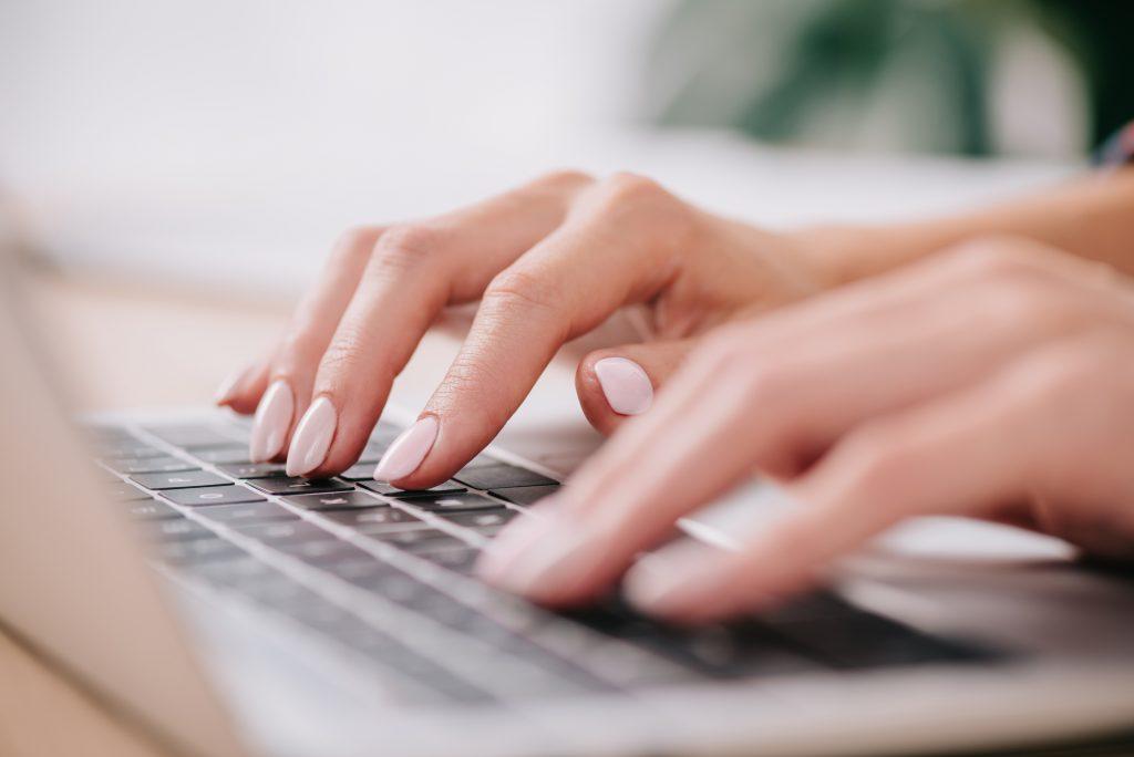 email copywriter typing on keyboard at computer