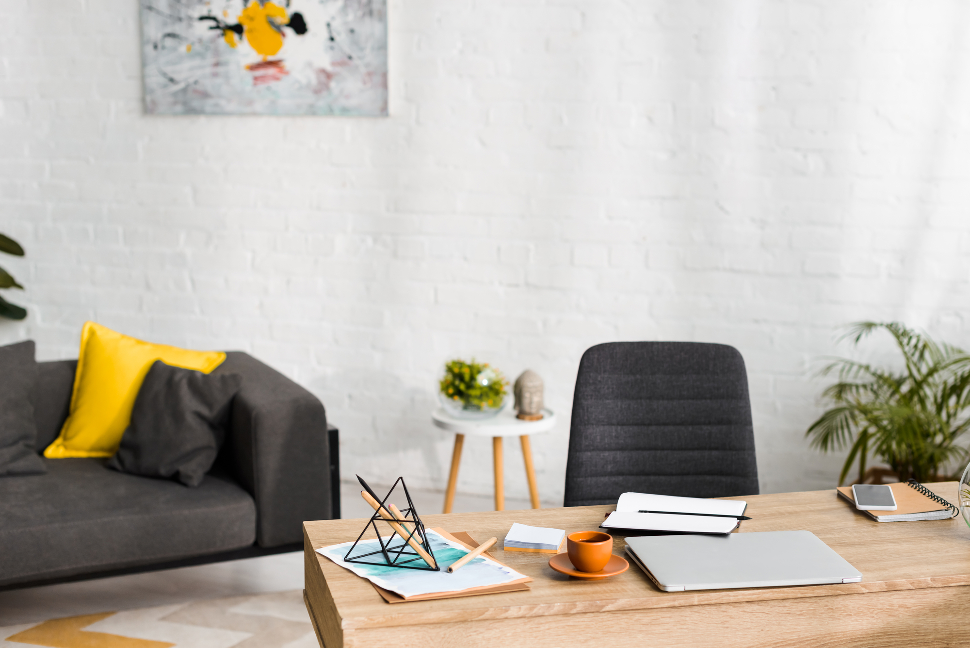 email copywriter desk with paper weight, pens, paper, chair, plant, desk, and couch