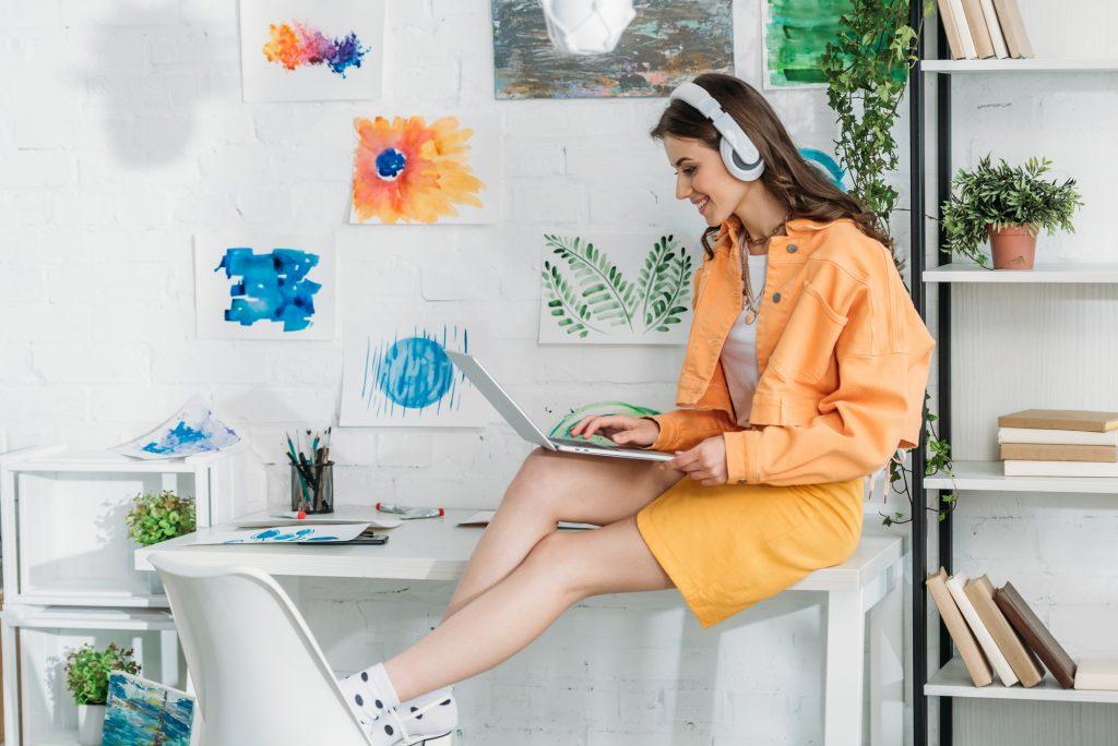 Email copywriter sitting on desk typing on laptop.